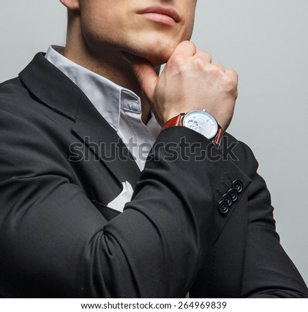 Portrait of handsome man in jacket with wrist watch on his hand - stock photo