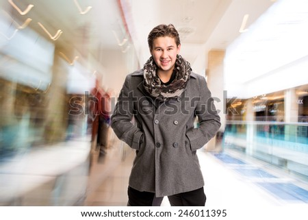Portrait of handsome man in scarf and coat in the mall - stock photo