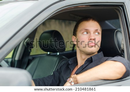 Portrait of handsome man in the car. - stock photo