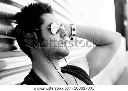 Portrait of handsome man in urban background with aviator sunglasses