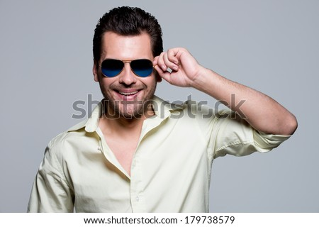Portrait of handsome man in yellow shirt wearing sunglasses poses in the studio. - stock photo