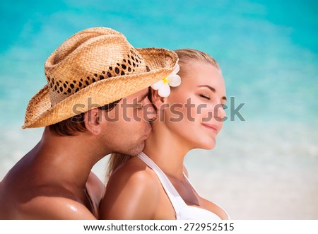 Portrait of handsome man kissing his nice young wife, closed eyes of pleasure, enjoying each other on the beach, summer vacation on exotic resort - stock photo