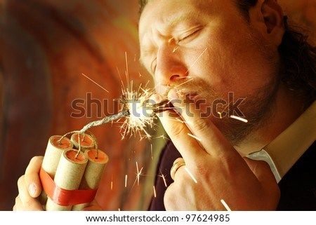 portrait of handsome man lighting a cigar from the dynamite - stock photo