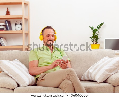 Portrait of handsome man listening to music and using mobile or smart phone at home. Happy man spending his weekends sitting on sofa or couch. - stock photo