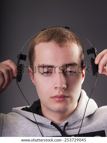 Portrait of handsome man listening to sad music in headphones on gray background - stock photo