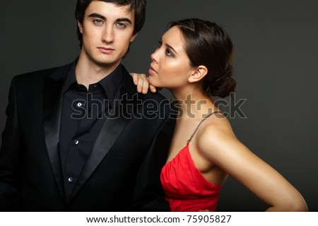 Portrait of handsome man looking at camera with beautiful woman near by looking at him - stock photo
