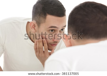 portrait of handsome man looking into the mirror and touching his smooth face