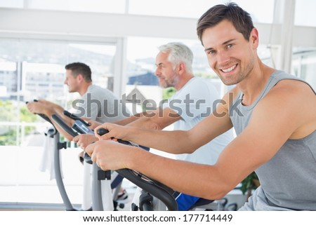Portrait of handsome man on exercise bike in fitness club - stock photo