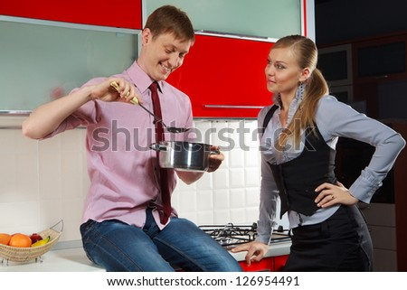 Portrait of Handsome man preparing food for his girlfriend in kitchen - stock photo