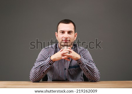 Portrait of handsome man sitting at the table - stock photo
