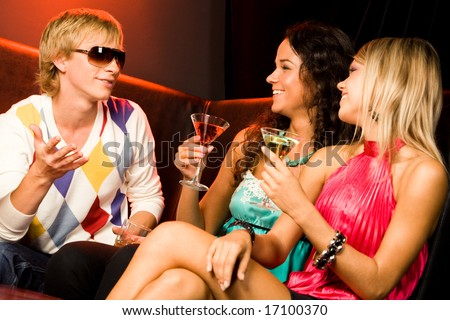 Portrait of handsome man speaking something to pretty women at party