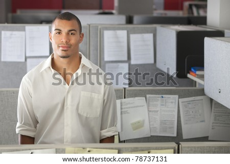 Portrait of handsome man standing in office cubicle - stock photo