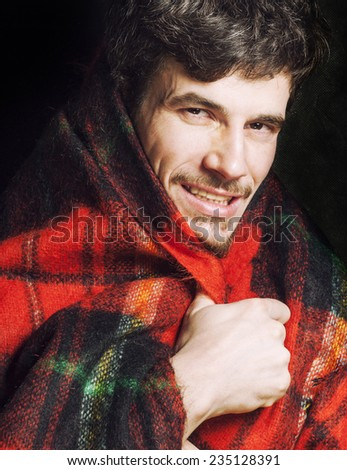 portrait of handsome man warmed up in scarf christmas colored, smiling - stock photo