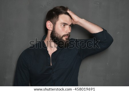 Portrait of handsome man with beard. confident man correcting haircut