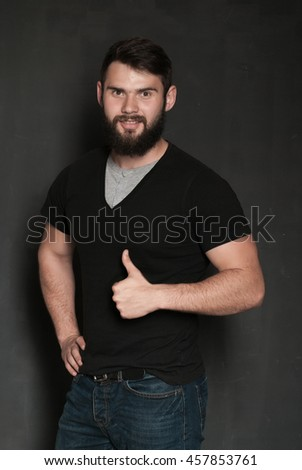 Portrait of handsome man with beard. Confident muscular man in black t-shirt on black background
