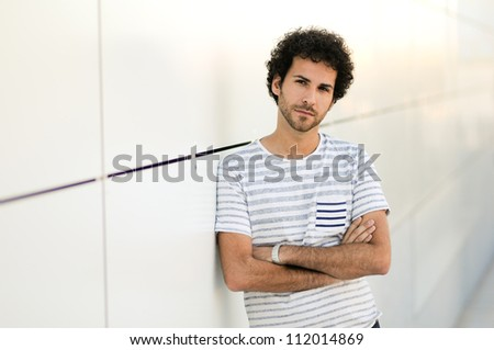 Portrait of handsome man with curly hairstyle in urban background - stock photo