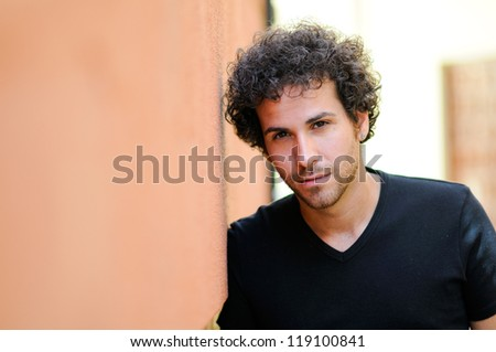 Portrait of handsome man with curly hairstyle in urban background