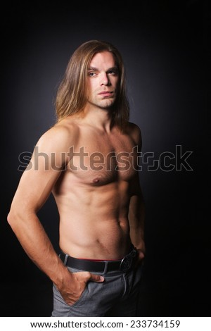 portrait of handsome man with long hair, torso naked on black background   - stock photo