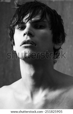 Portrait of handsome man with wet hair on gray wall background. Black and white portrait. - stock photo