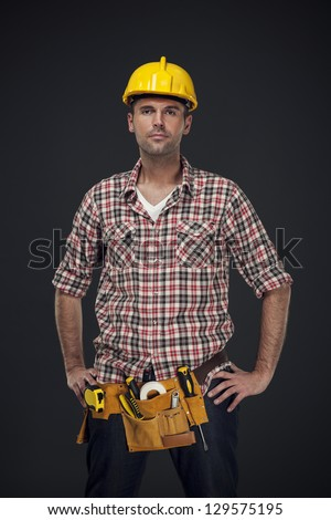 Portrait of handsome manual worker with tool belt - stock photo