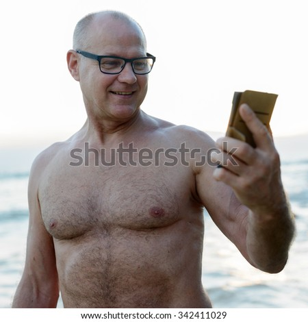 Portrait of handsome mature Caucasian man outdoors taking selfie picture with mobile phone