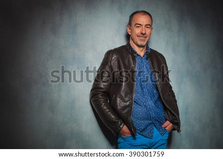 portrait of handsome mature man in leather jacket standing in gray studio background with both hands in pockets while looking at the camera - stock photo