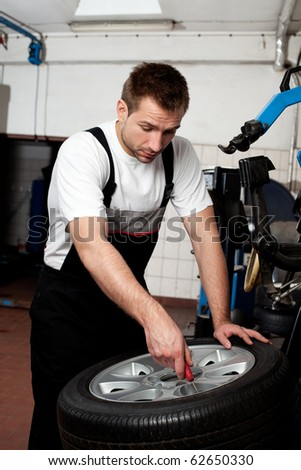Portrait of handsome mechanic fixing tire in car service - stock photo
