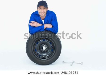 Portrait of handsome mechanic leaning on tire over white background - stock photo