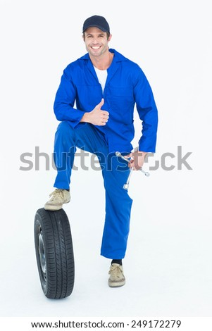 Portrait of handsome mechanic with tire and wheel wrenches gesturing thumbs up over white background