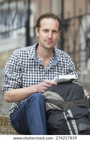 Portrait of handsome mid adult man with book and backpack sitting against buildings in city - stock photo