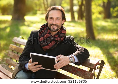 Portrait of handsome middle-aged man sitting on the bench with tablet PC. Attractive man in black coat enjoys working outdoors. - stock photo