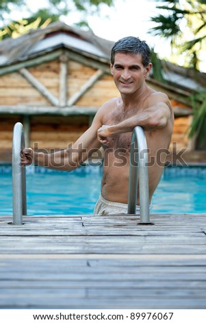 Portrait of handsome middle aged man standing in the swimming pool - stock photo