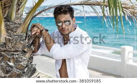 Portrait of handsome model wearing aviator sunglasses in summer scenery  - stock photo
