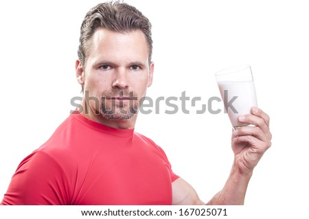 Portrait of handsome muscular Caucasian man with goatee wearing red athletic shirt holding glass of milk on white background - stock photo