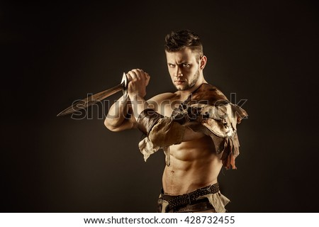 Portrait of handsome muscular gladiator with sword. Isolated. Studio shot. Black background - stock photo