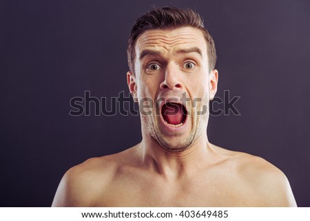 Portrait of handsome naked man looking at camera and screaming, on a dark background