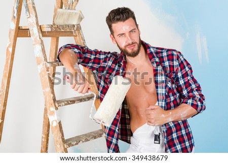 Portrait of handsome painter with unbuttoned shirt, paint roller and vintage ladder, posing and looking at camera