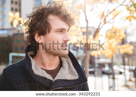 Portrait of handsome pensive attractive thoughtful curly guy in black jacket walking in town - stock photo