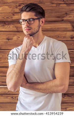 Portrait of handsome pensive young man in eyeglasses looking away and thinking, against wooden wall - stock photo