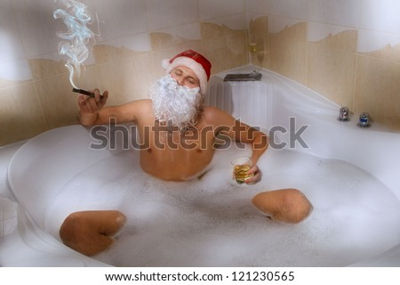 Portrait of handsome Santa with whiskey and cigar sitting in a hot bubble bath tub. Relaxing after a long night of deliveries.