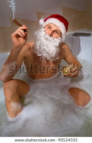 Portrait of handsome Santa with whisky and cigar sitting in a hot bubble bath tub. Relaxing after a long night of deliveries.