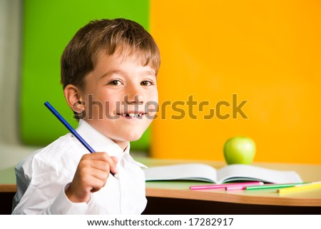 Portrait of handsome schoolboy holding pencil in hand and looking at camera - stock photo