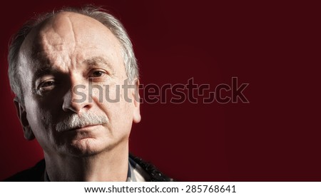 Portrait of handsome senior man with a tired expression on red background with copy-space
