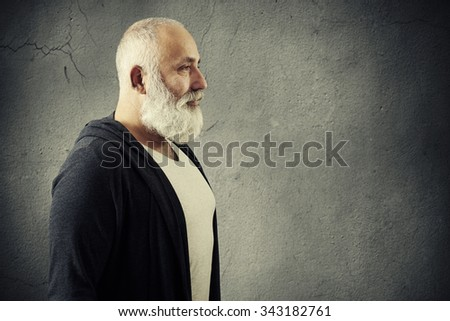 portrait of handsome senior man with grey-haired beard with empty copyspace on right over grey background - stock photo