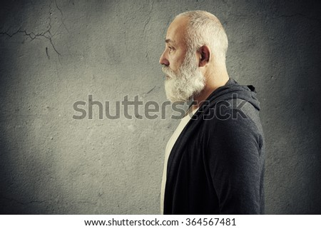 portrait of handsome senior man with grey-haired beard with empty copyspace over grey background - stock photo