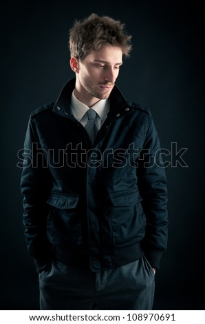 Portrait of handsome, serious man against dark background. - stock photo