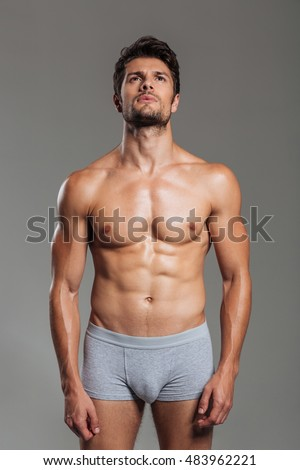 Portrait of handsome sexy athletic man in underwear posing and looking up isolated on a gray background
