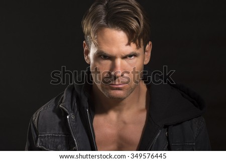 Portrait of handsome sexy Caucasian man with bold eyes and serious expression wearing open jacket revealing pectoral definition on black background - stock photo