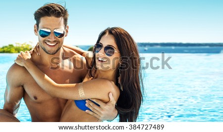 Portrait of handsome smiling couple having fun in swimming pool wearing sunglasses - stock photo