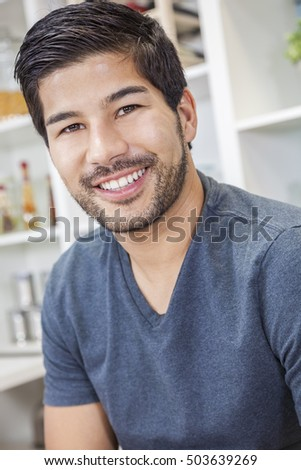 Portrait of handsome smiling young Asian man with a beard